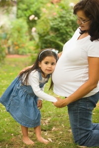 [Photo of little girl with her head resting on to her mother's pregnant belly]